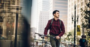 young man walking a bicycle in the city