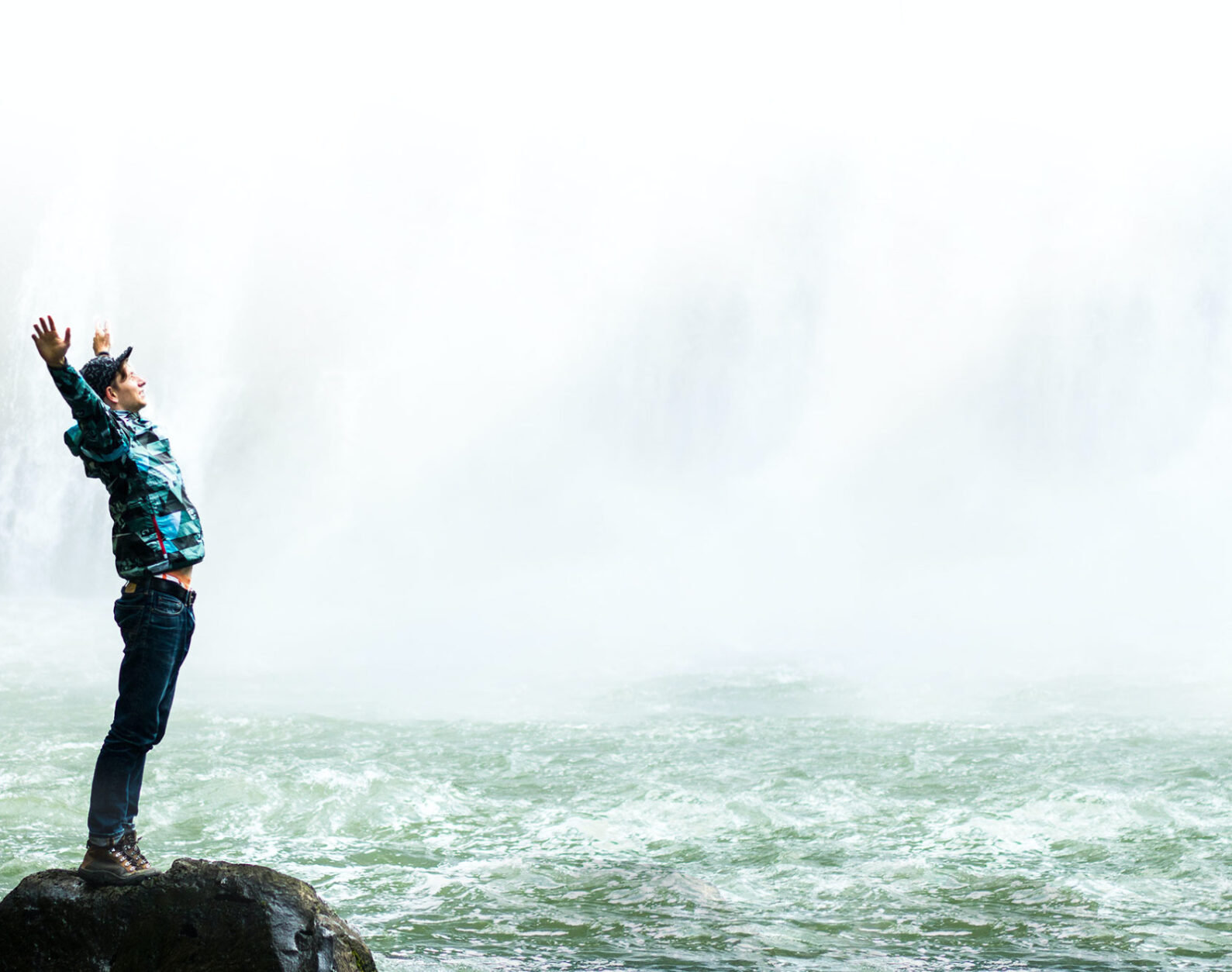 Man With Arms Open at Bottom of Waterfall