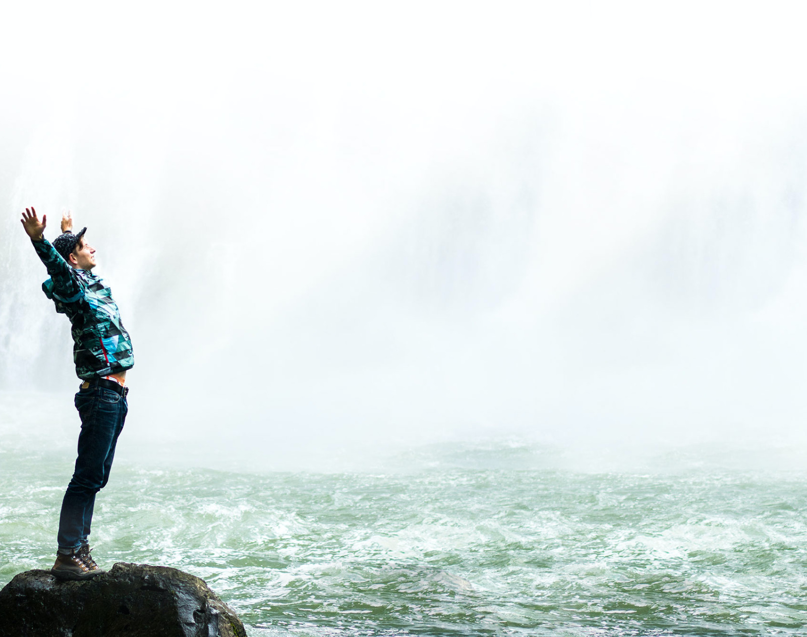 Man Stretching Below a Waterfall